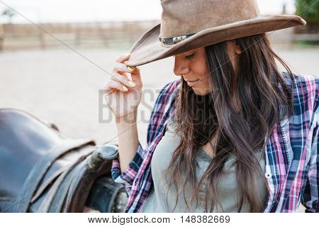 Close up portrait of a pretty cowgirl leaning on fence at ranch