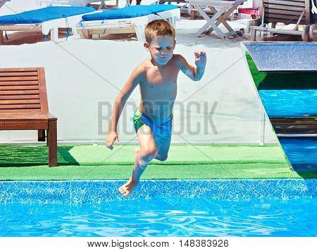 Small Boy Jumping Into Resort Pool