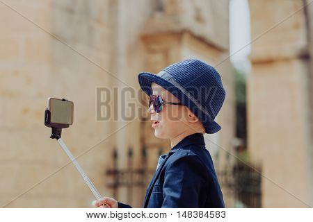 happy little boy taking selfie picture on travel in Europe, family vacation and technology