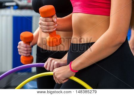 Women with bare belly working dumbbells and hoop at gym. Group of people working with dumbbells and hoop his body at gym.