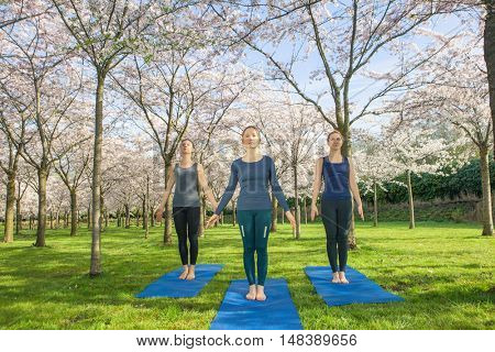 Three young women standing in  a mountain pose, tadasana.  Tadasana is usually the starting position for all the standing poses.