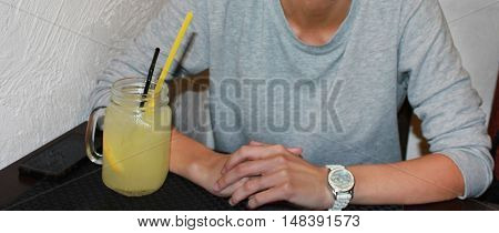 Cropped portrait of young person woman man in gray pullover sitting at the table having a drink at the restaurant bar background