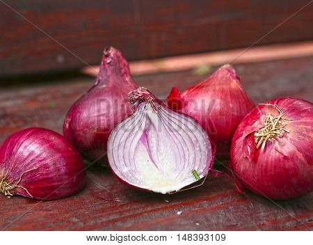 red onions cut and whole on the wooden country bench close up photo