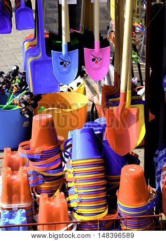 a selection of brightly coloured buckes and spades on sale in a shop