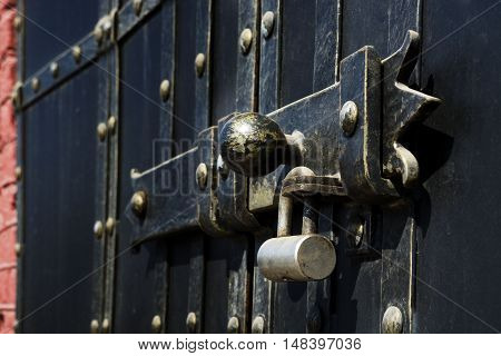 Black iron gate with brass squares and a lock with a latch