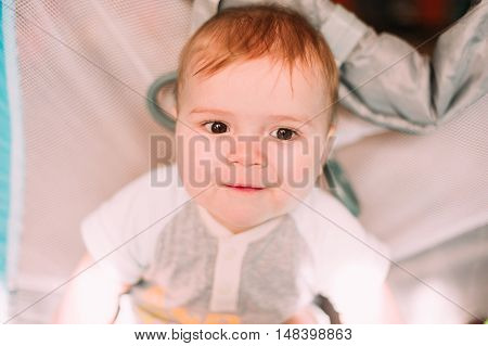 Cute little baby boy playing in colorful playpen indoors. Beautiful child having fun at nursery. poster