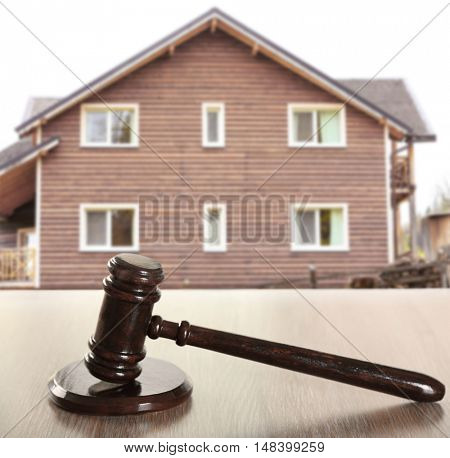 Gavel on wooden house background