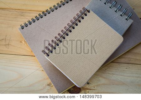 Recycled paper notebook superimposed three books on a wooden table