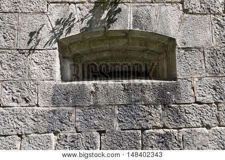 Detail of a loophole (rifle slit) in a grey fortified wall. Austrian fortress