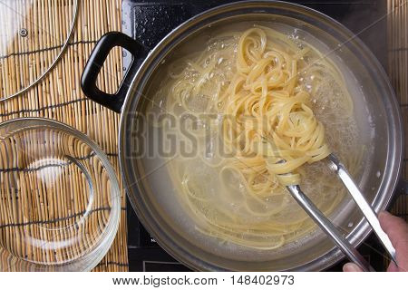 Chef cooking spaghetti in the pan / cooking spaghetti concept