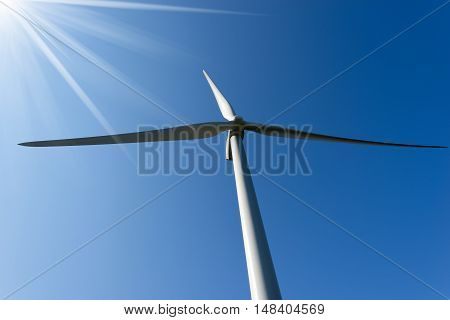 Detail of a white wind turbine with sun rays on a clear blue sky
