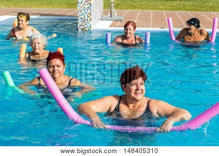 Group of senior citizens at aqua gym rehabilitation session in outdoor swimming pool. People working out with soft foam color noodles.