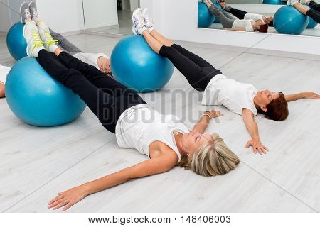 Group of Middle aged women in health center doing leg exercises with fitness balls on floor.
