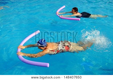 Top view of two senior women doing swimming exercise with soft foam noodles in outdoor swimming pool.