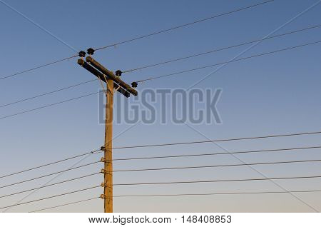 Power line on wooden poles at sunset