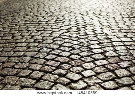Perfect cobblestone streets of the city. Paving stone roadbed made with small stone blocks.