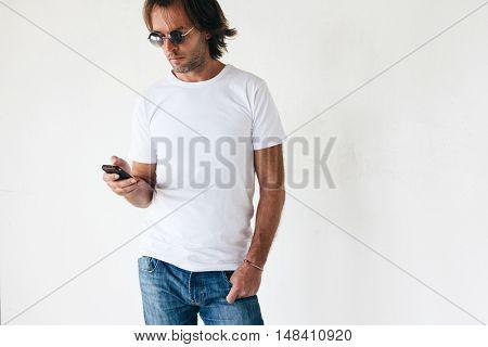 Man wearing blanc t-shirt posing against white wall, toned photo, front tshirt mockup on model