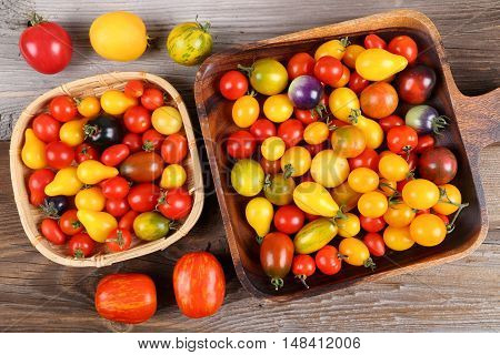 Colorful different kind tomatoes on wooden background.