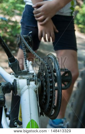 boy repairing a bicycle wheel from the outdoors in summer