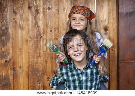 Happy kids repainting the wood shed - smiling with paintbrushes