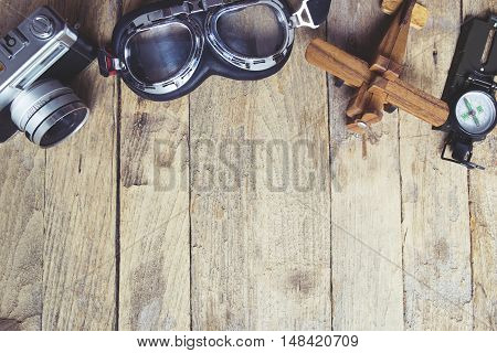 Vintage retro travel background. Retro camera glasses balsa wood model airplane and compass on wooden table background.
