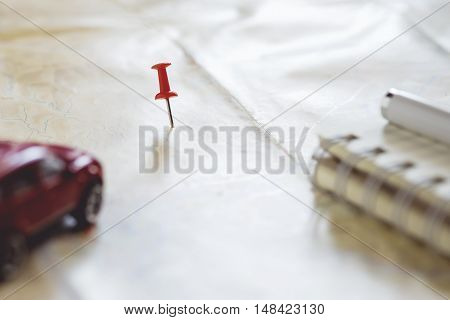 Travel concept background.Red pushpin push point of location destination on map with blured red car notebook and pen.