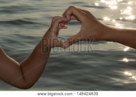 Two children with the help of their hands joined fingers heart symbol and mutual undying love against the backdrop of a beautiful sunset