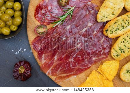 Plate with spanish jamon and chorizo tapas, picnic table