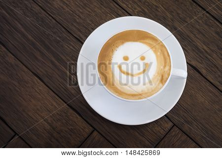 White Cup Of Latte Art Happy Smile Face On Brown Wooden Table Background.