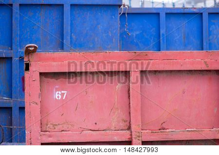 A background of red and blue sand tipper containers at a construction site. Construction and transport concept.