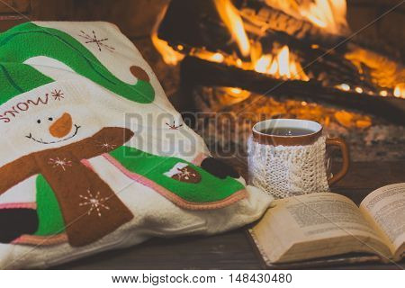 Antigue books, tea hot drink in mug, pillow with Christmas decor near fireplace. Fireplace as background. Christmas or winter concept.