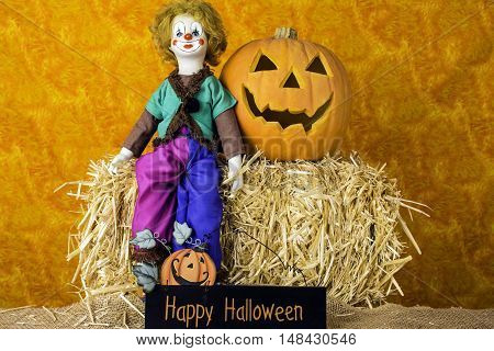 porcelain clown doll sitting on bale of straw with jack-o-lantern and happy halloween sign with orange background