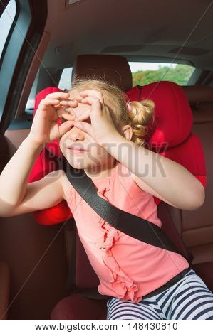 Portrait Of Happy Little Child Girl Sitting Comfortable In Car Seat With Safety Belts Enjoying Ride