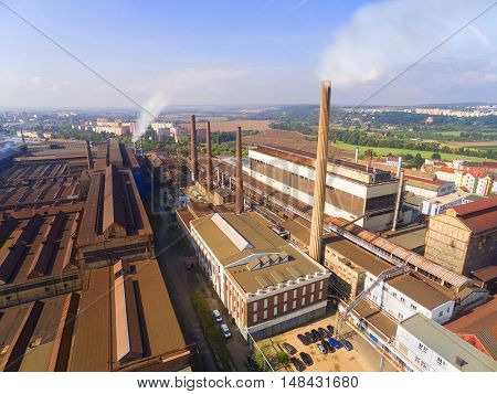 Aerial view of industrial zone with fuming chimneys. Heavy industry from above. Steelworks in Pilsen, Czech Republic, European Union.