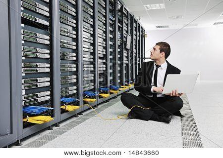 Ingeniero joven hombre de negocios con ordenador portátil de aluminio fino moderno en la sala de servidores de red