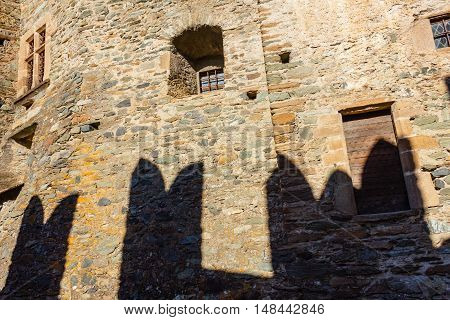 FENIS,ITALIA-SEPTEMBER 5.The facade of the castle of Fenis in Aosta Valley with its city walls and its defensive towers on September 5 2016 in Fenis.The  shadows of the battlements drawn on the towers   illuminated by the sun