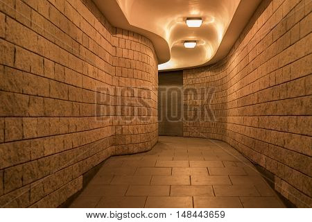a curving pedestrian tunnel (subway) in the City of London, at night