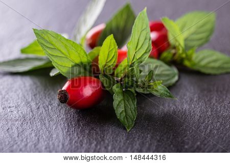Several Red Hips With Herbs Placed On Black Slate Stone