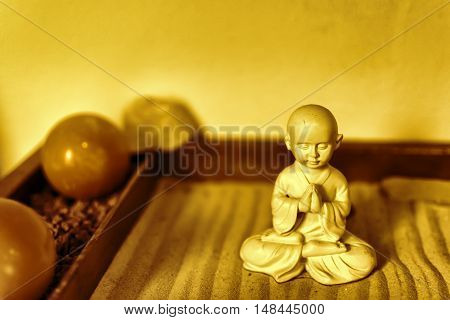 Buddha Statue in Lotus Position Sitting on the Sand. Ayurveda Concept. Buddha in Zen Garden With Smooth Lines in Sand.