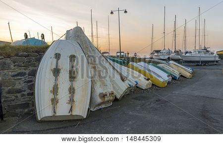 Row of upturned dinghy's, against a wall, with a background of a setting sun, and ship masts