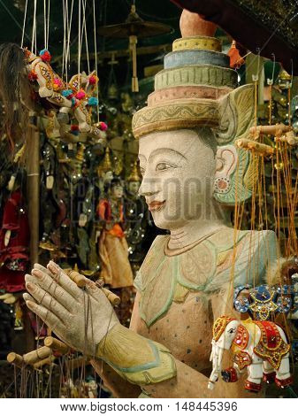 Bleached effect close up of traditional ornate hand-made Burmese string puppet hanging in souvenir shop