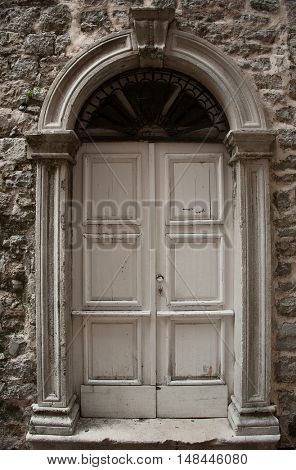 wooden old door with stone door aperture into stone ancient building
