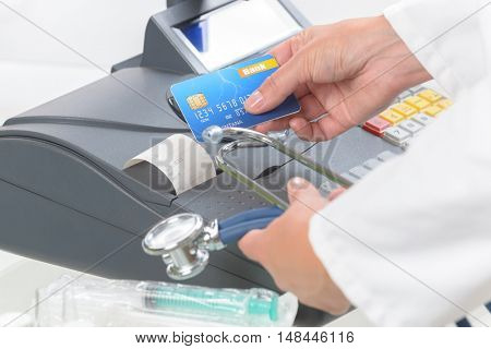 pharmacist or medical doctor holdnig stethoscope and using cash register and credit card at pharmacy or surgery