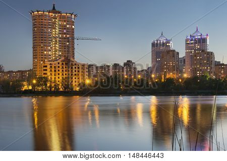 Donetsk City downtown skyline at dusk with skyscrapers illuminated over Kalmius river. Modern skyscrapers. new building construction lights and reflections at water.