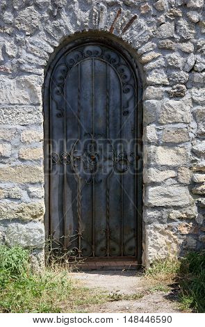 antique old wrought iron door on rubble wall