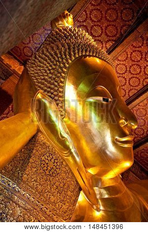 The Big golden Reclining Buddha at Wat Pho in Bangkok Thailand. The image of reclining Buddha is 15 m high and 43 m long.