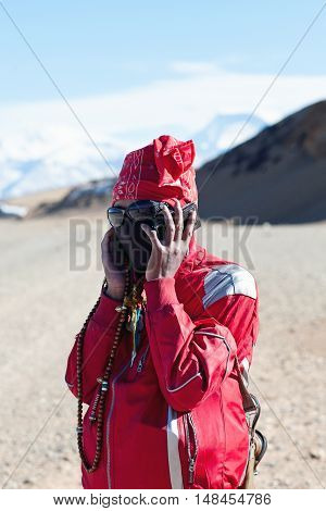 NGARI, TIBET - MAY 7: Tibetan pilgrim walking on the road across holy Manasarovar lake on May 7, 2013 in Tibet Autonomus Region of China