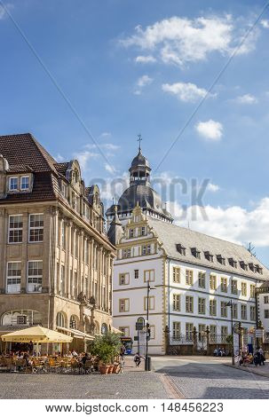 PADERBORN, GERMANY - SEPTEMBER 6, 2016: Cityscape of the historical center of Paderborn with people enjoying the sun at a cafe