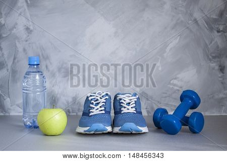 Sport shoes dumbbells apple bottle of water on gray concrete background. Concept healthy lifestyle sport and diet. Sport equipment.
