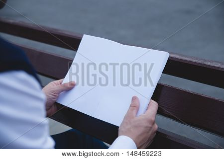 Mock up cover magazine, catalog, book. Man reading a blank magazine, catalog, book on the bench.